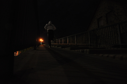 Runner going uphill in the dark